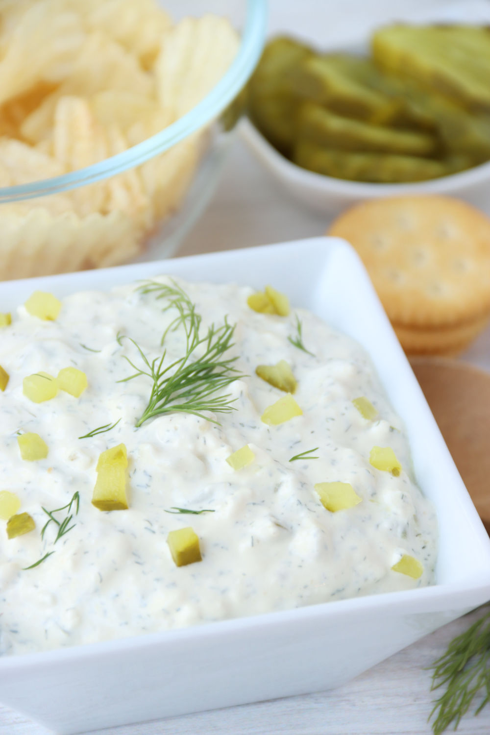bowl of dill pickle dip with crackers in background
