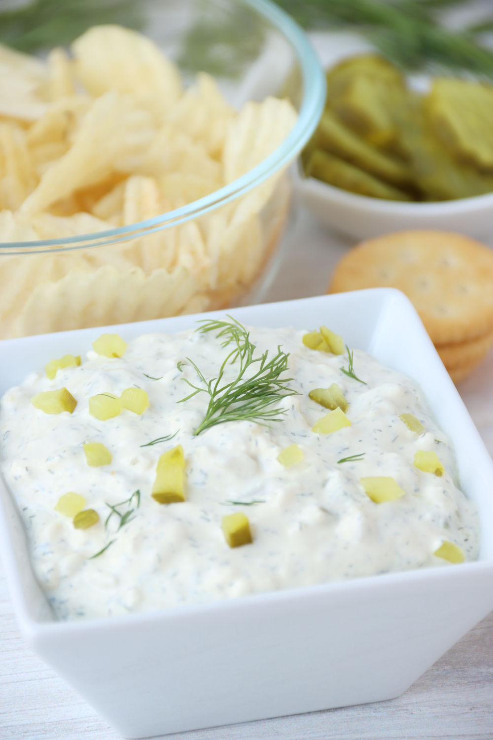 dill pickle dip with chips and crackers in the background
