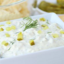 Bowl of dip with pieces of pickle and fresh dill