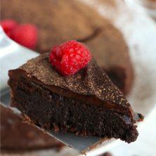 piece of flourless chocolate cake on cake server