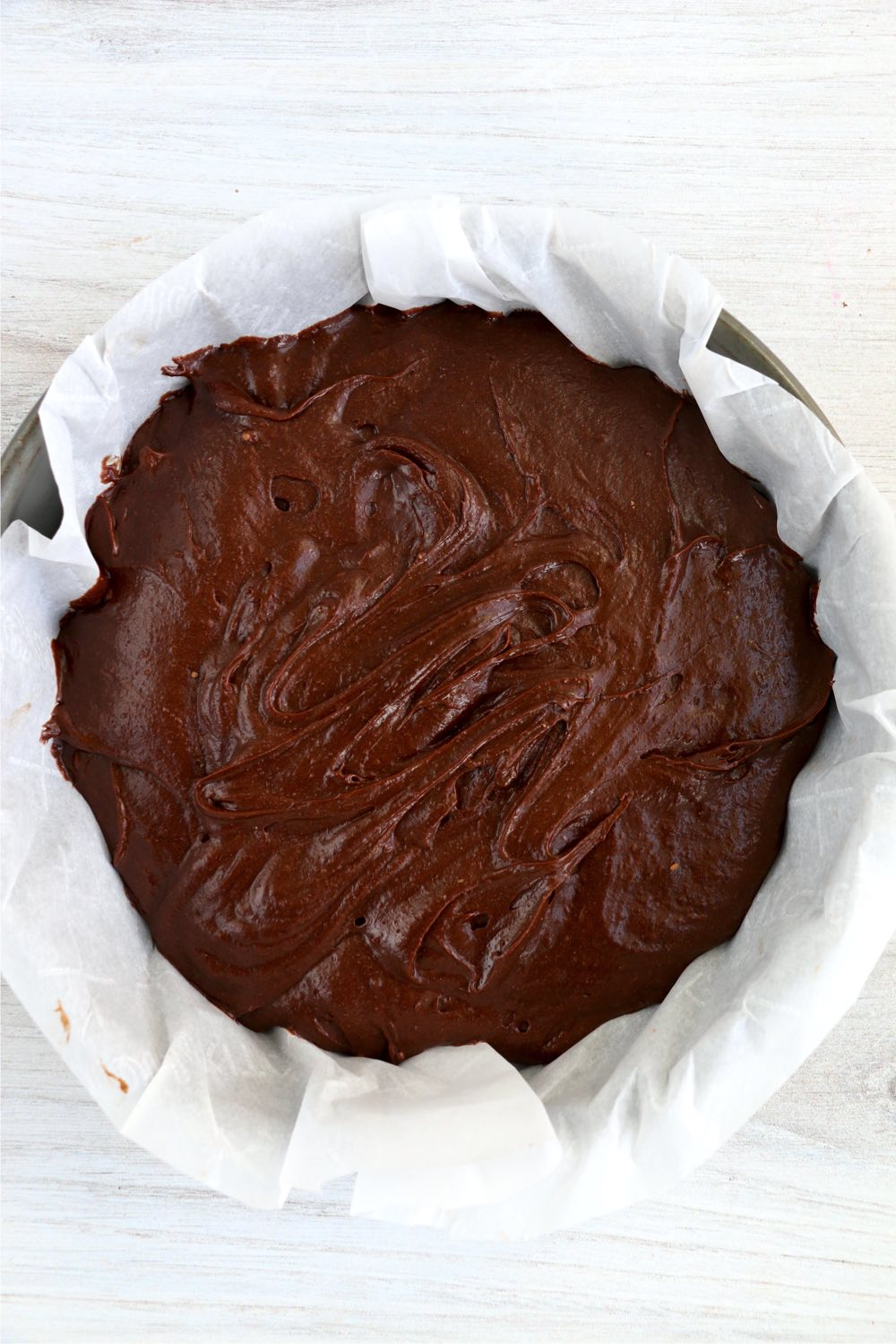 parchment paper lined pan with chocolate batter inside