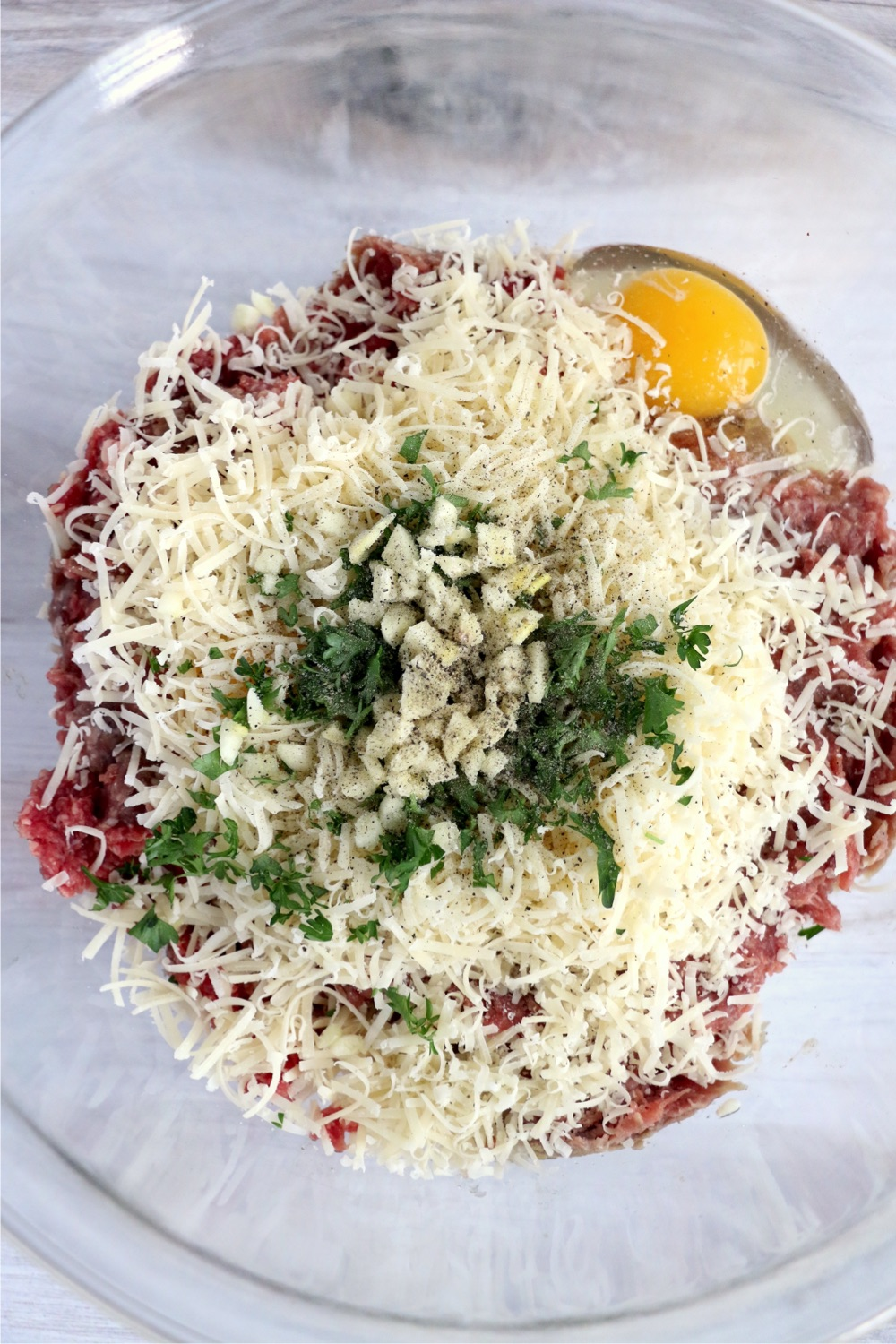 Mixing bowl filled with ground beef, ground pork, garlic, Romano cheese, parsley, salt and pepper