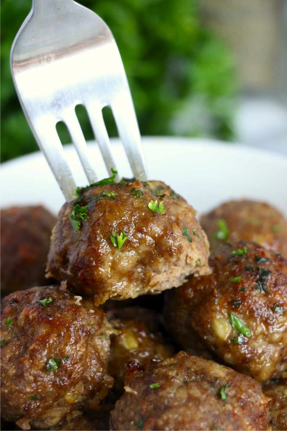 Fork picking up meatball in bowl
