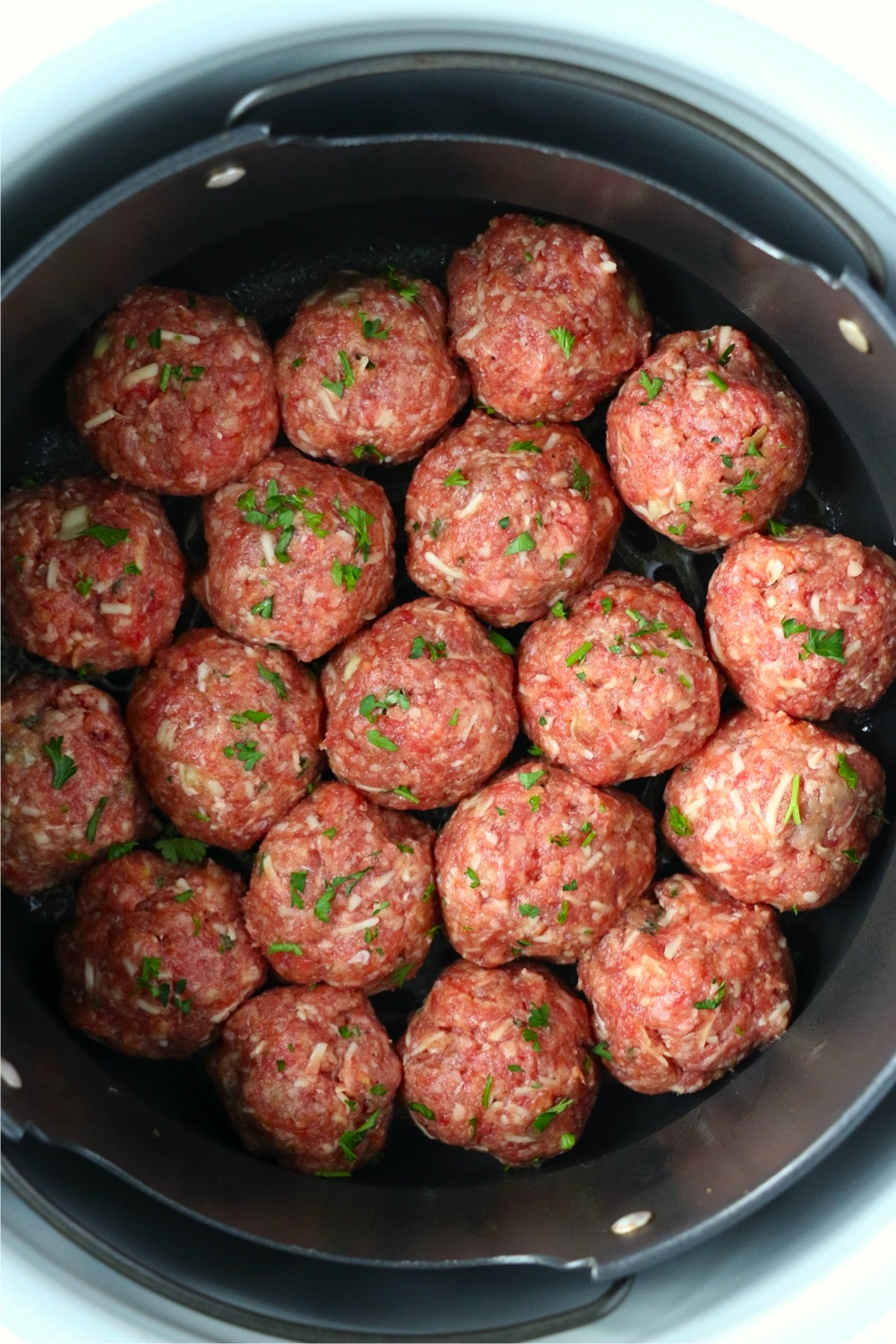 air fryer basket filled with uncooked meatballs