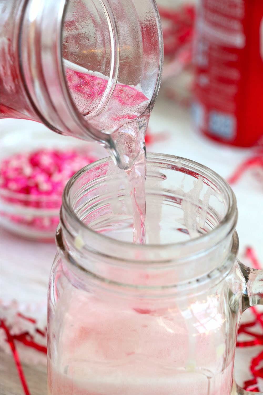 pouring cherry soda onto ice cream in a mason jar