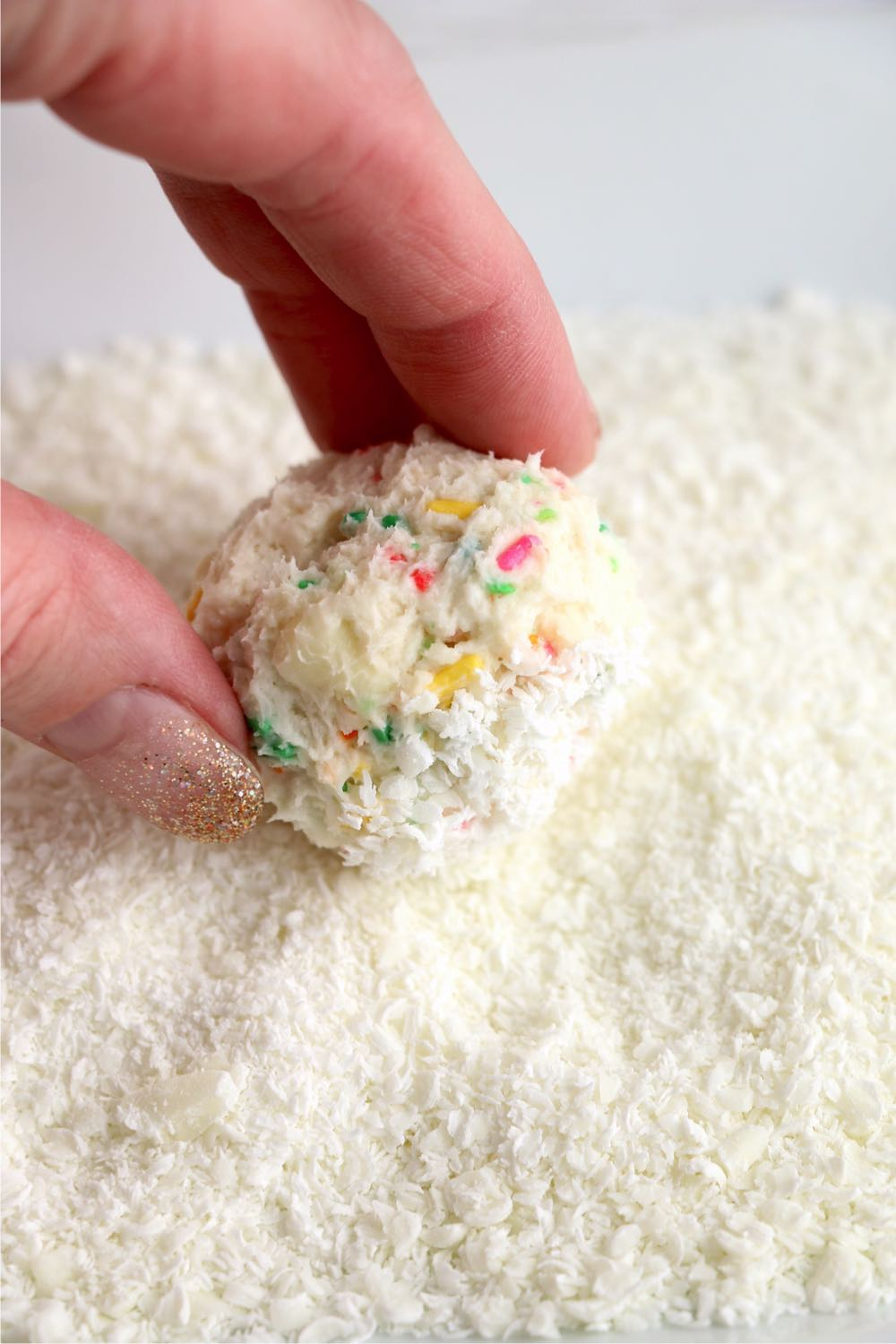 rolling cake ball in shaved white chocolate