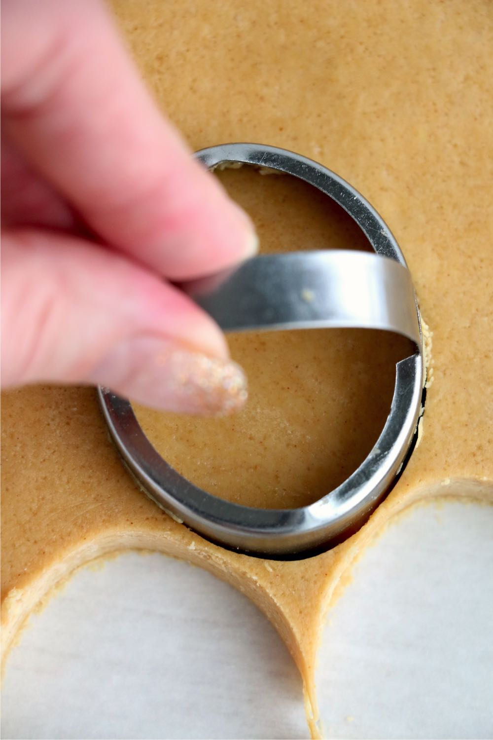 using an egg-shaped cookie cutter to cut out dough
