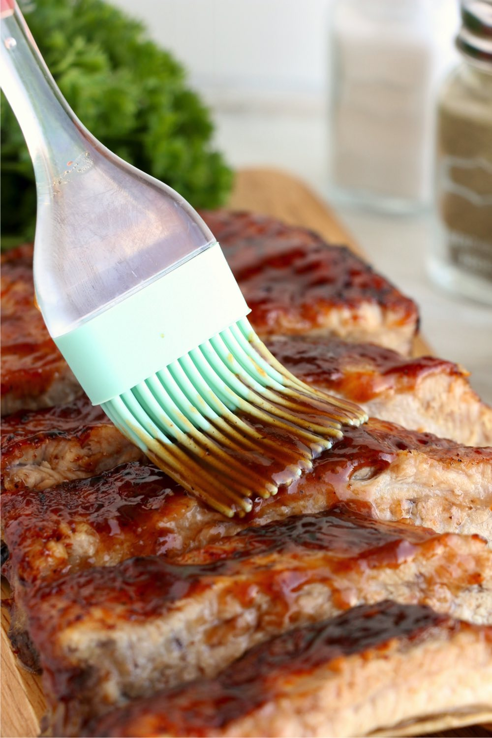 brushing rack of ribs with BBQ sauce