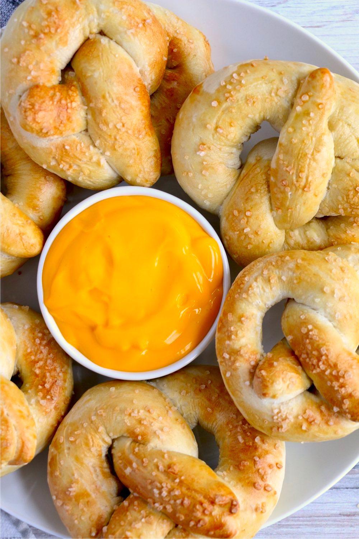 soft pretzels surrounding bowl of cheese dip