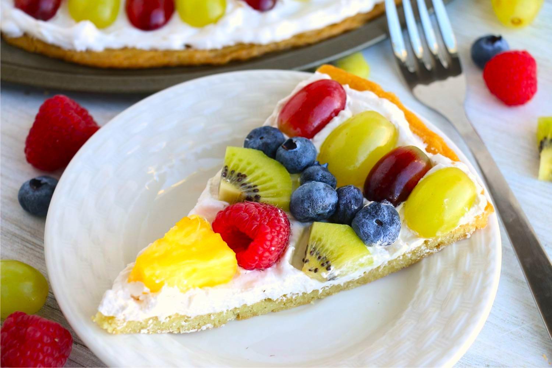 Slice of fruit pizza on a white dessert plate
