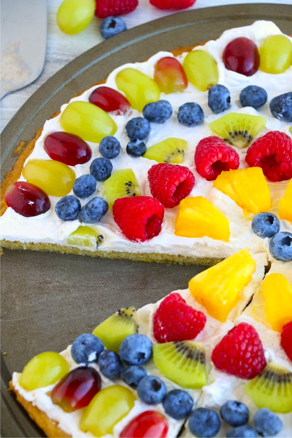 Fruit pizza with piece taken out