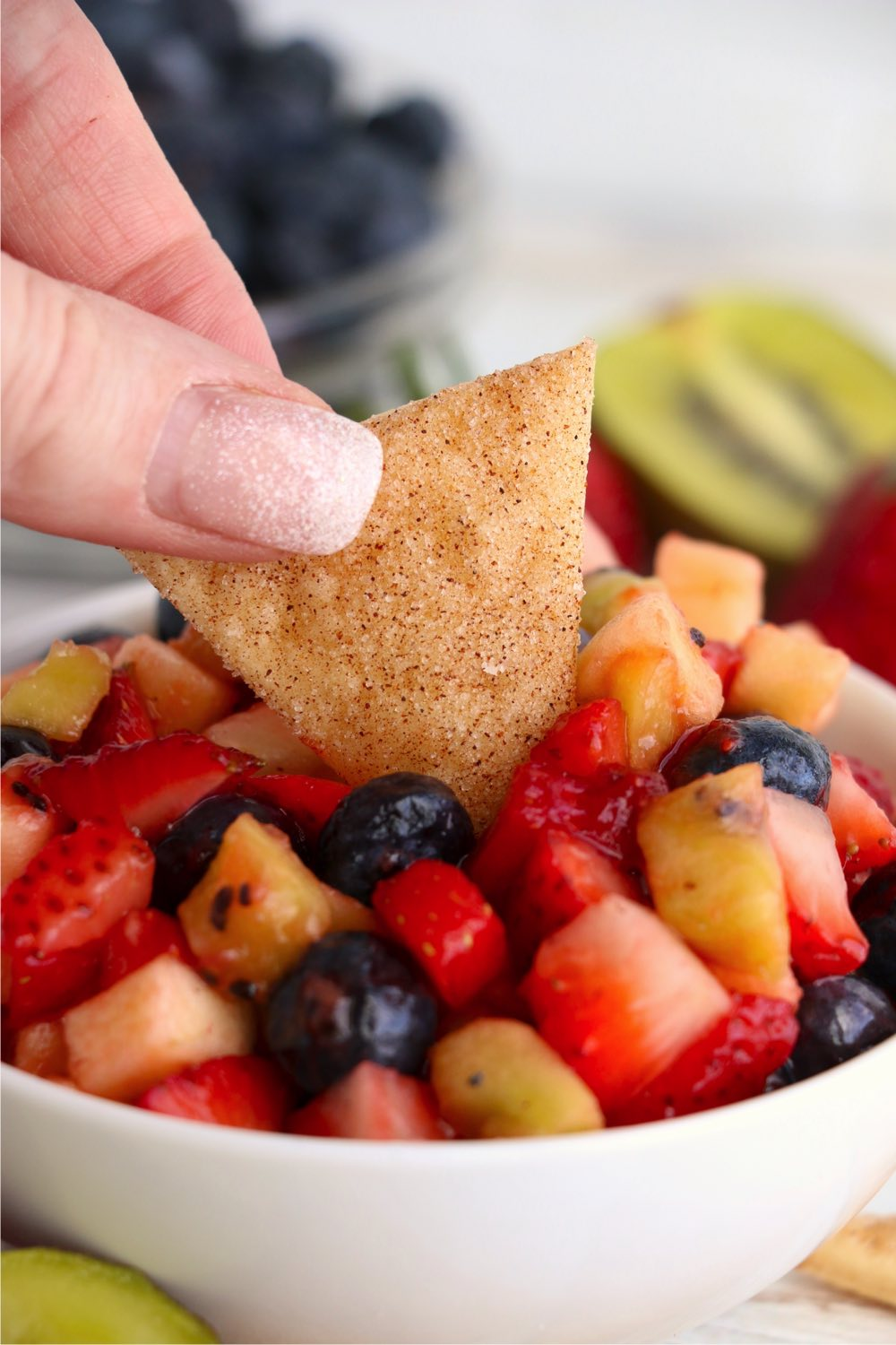 dipping a pie crust chip in fruit salsa