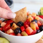 dipping a chip in a white bowl filled with fruit salsa