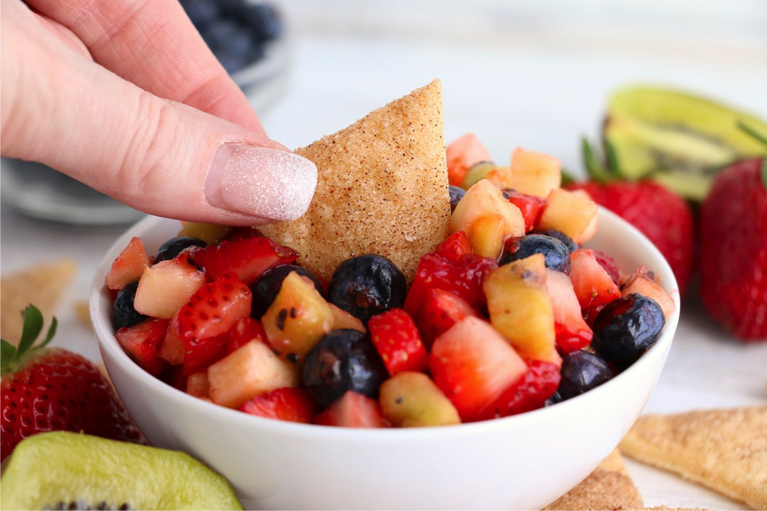 hand dipping pie crust chip into fruit salsa