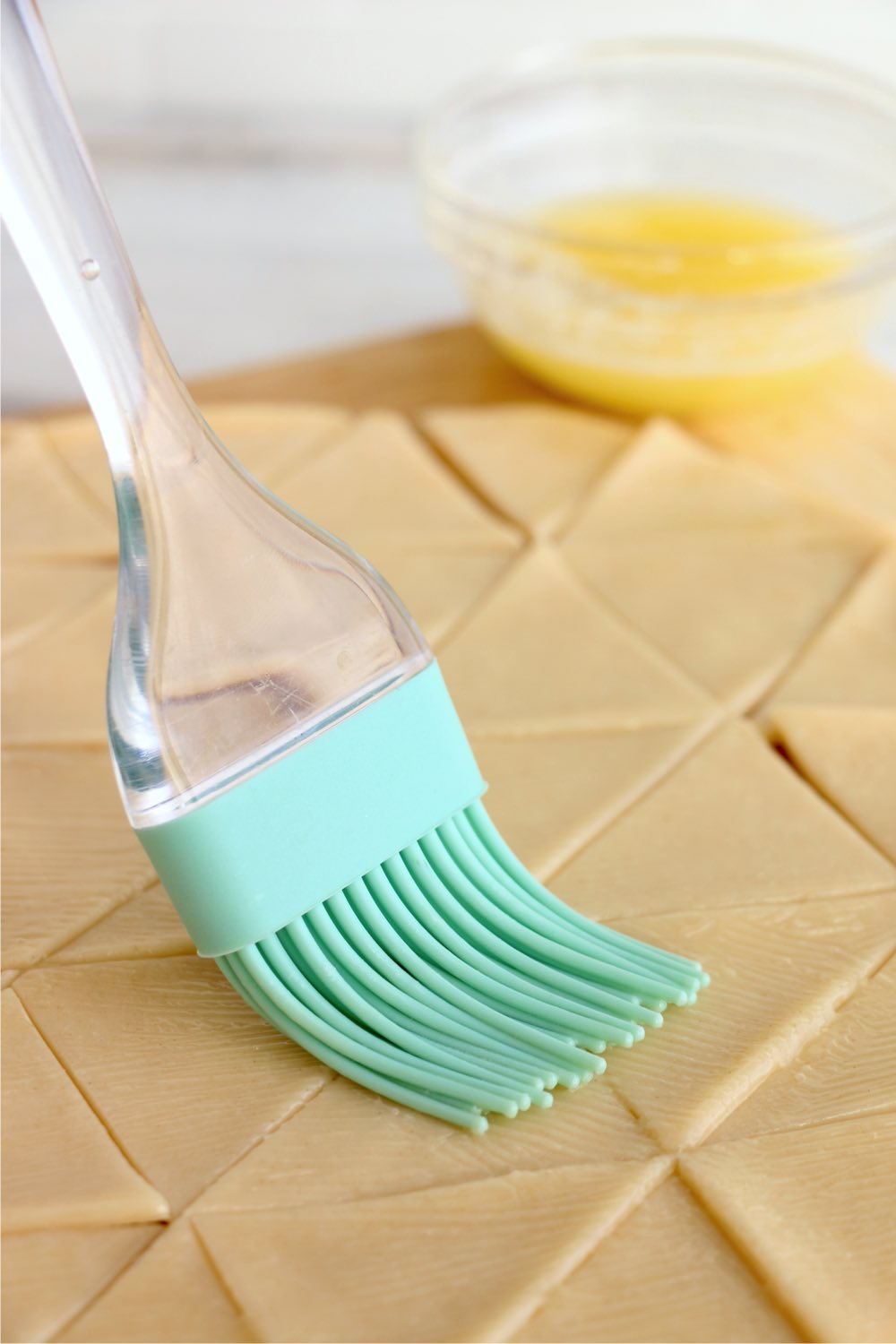 brushing pie crust dough with butter