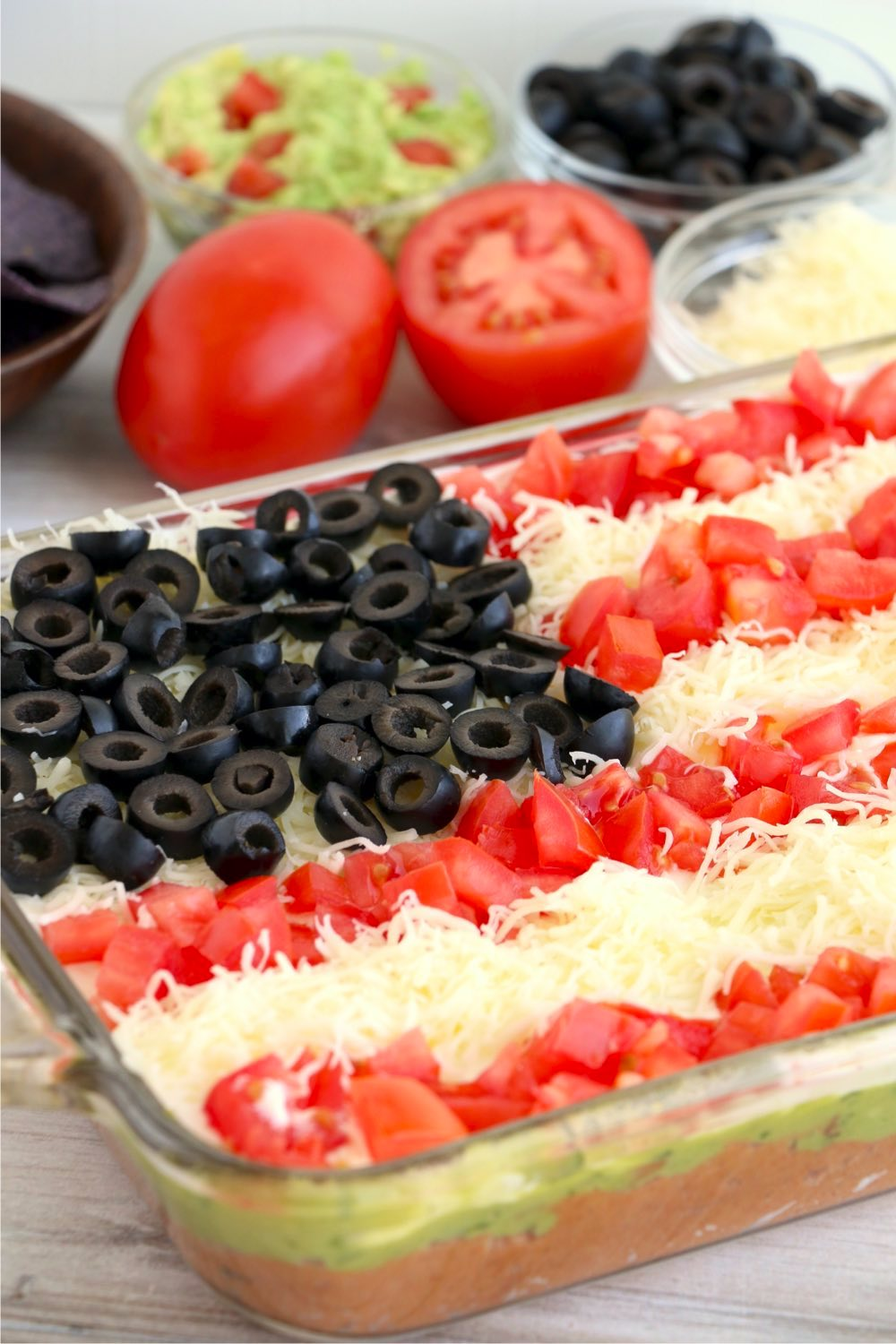 pan of layered taco dip with cheese and tomatoes in background
