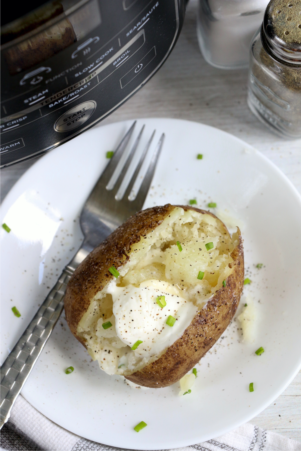 baked potato on a plate with a fork