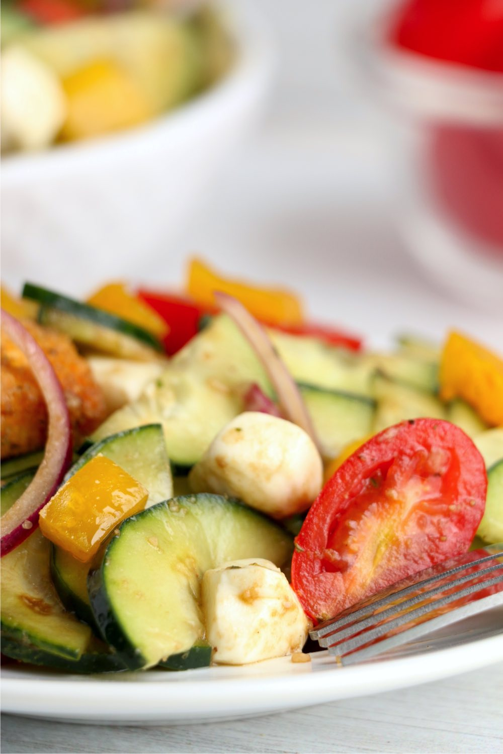 tomatoes, cucumbers and mozzarella in salad on white plate