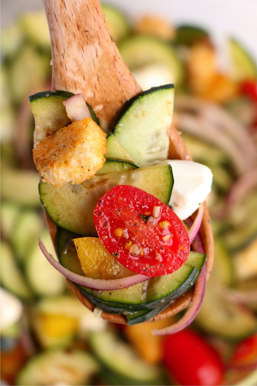 Panzanella Salad on a wooden spoon