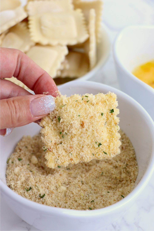 dredging ravioli in bowl of breadcrumbs