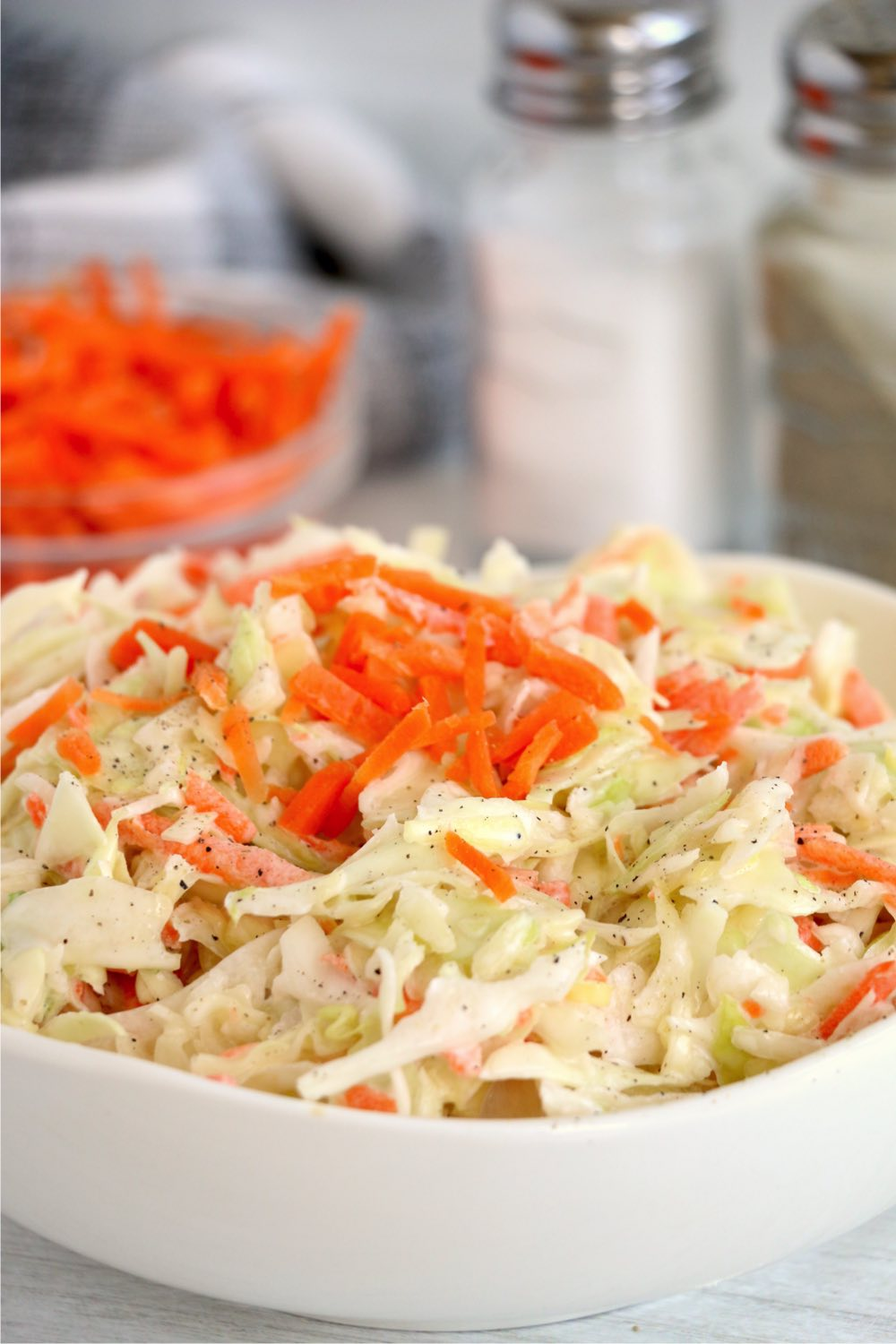 white bowl of coleslaw with salt and pepper in background