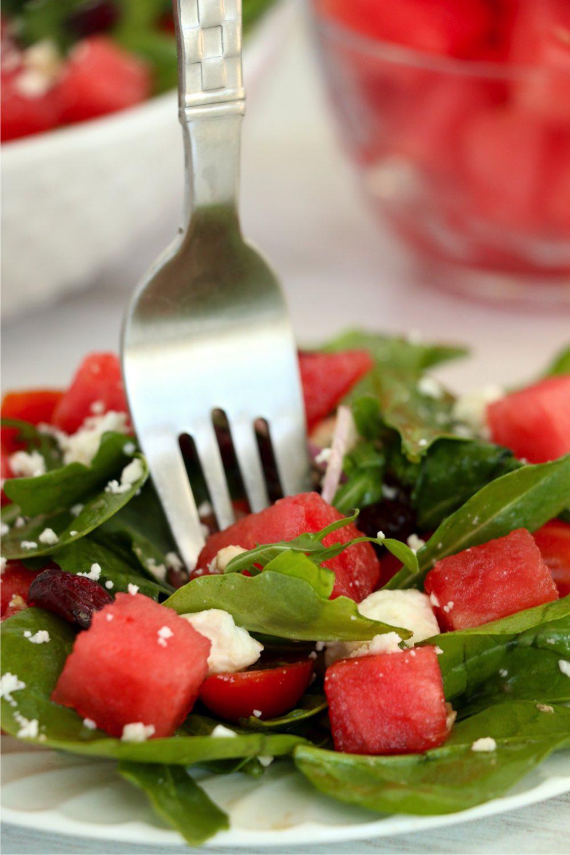 fork sinking into watermelon feta salad