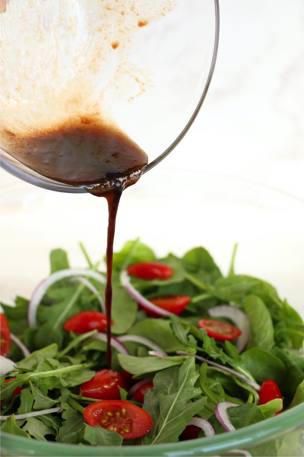 drizzling balsamic dressing on salad
