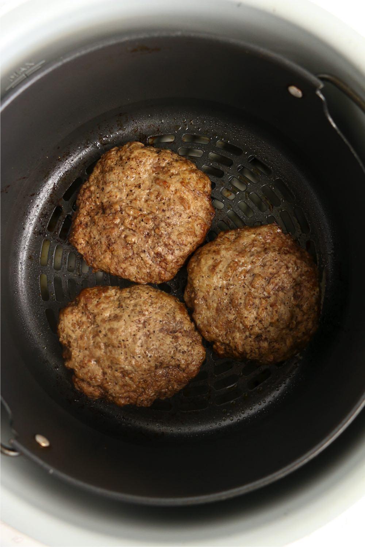 Cooked burgers in Ninja Foodi air crisp basket