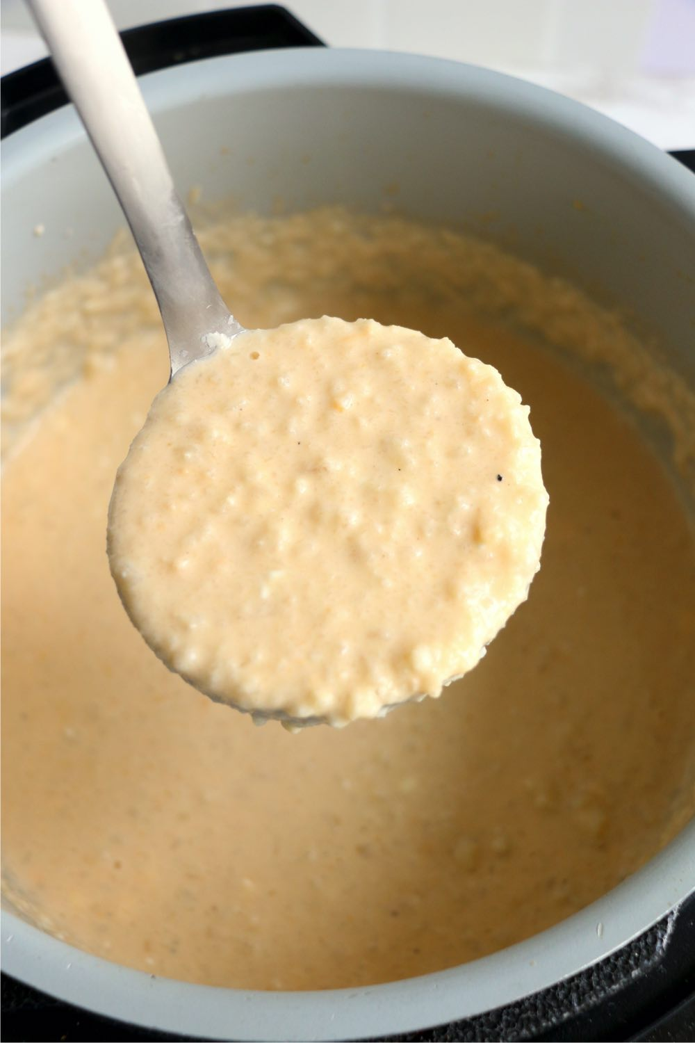 ladle with cheesy cauliflower soup