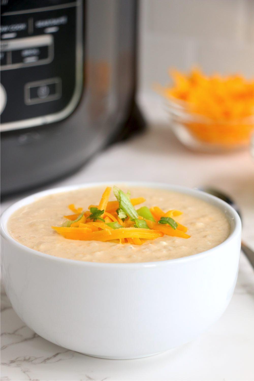 Bowl of cauliflower soup in front of Ninja Foodi