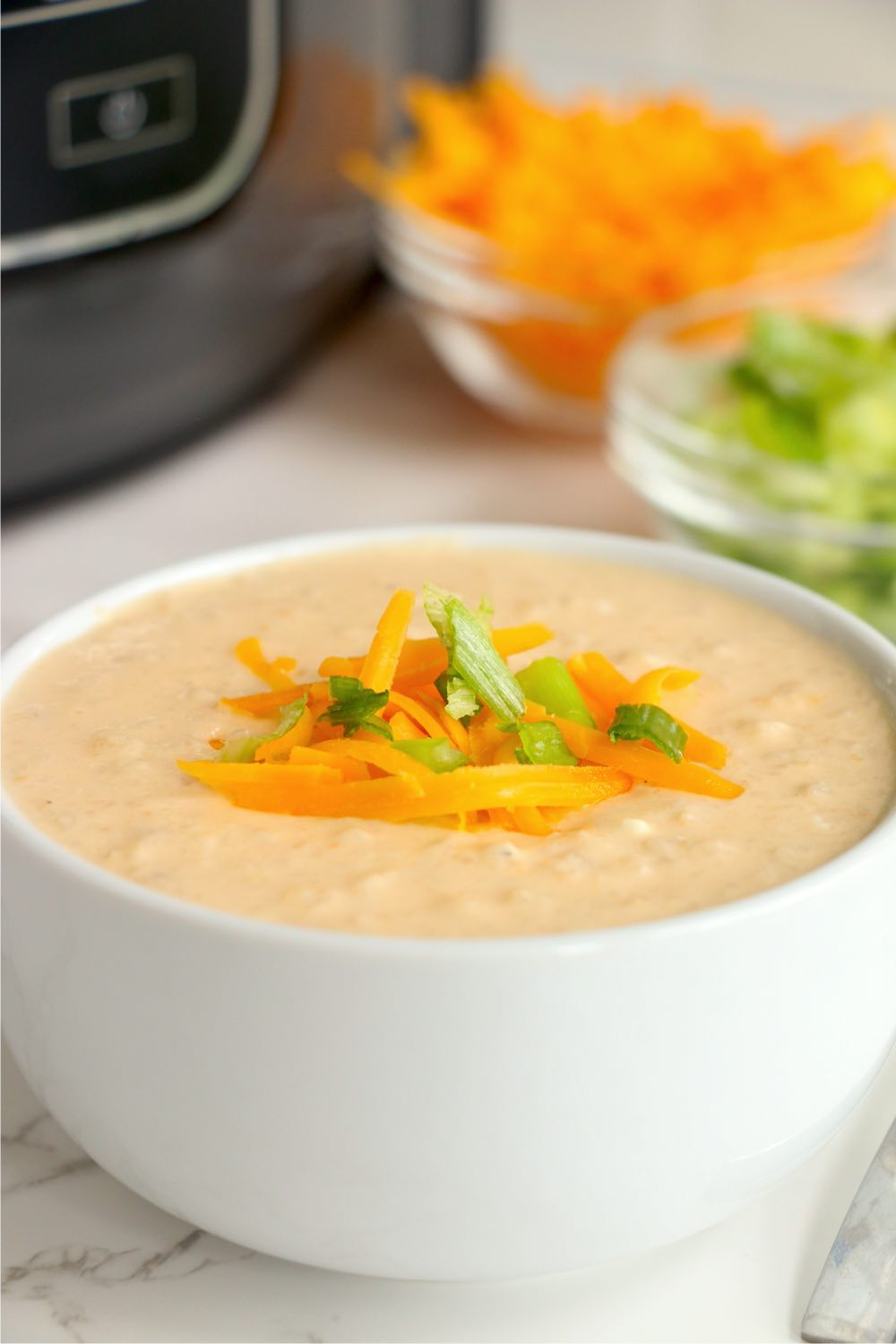 bowl of cheesy cauliflower soup garnished with shredded cheese and green onions