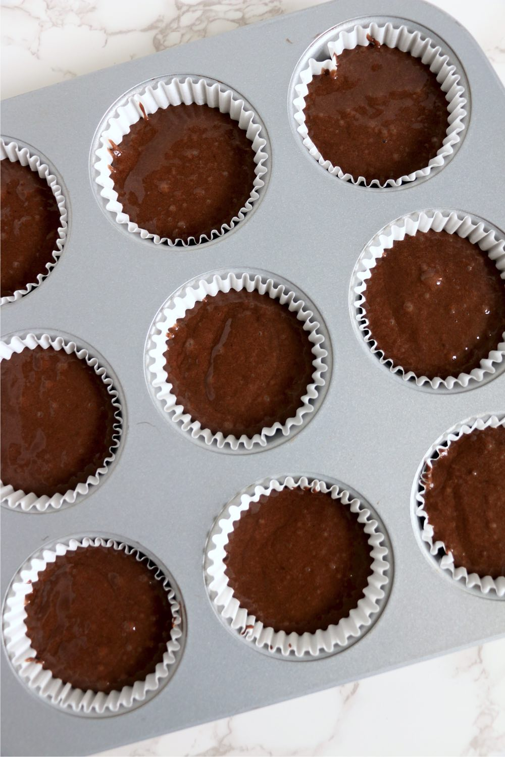 muffin tin cavities filled with cupcake batter